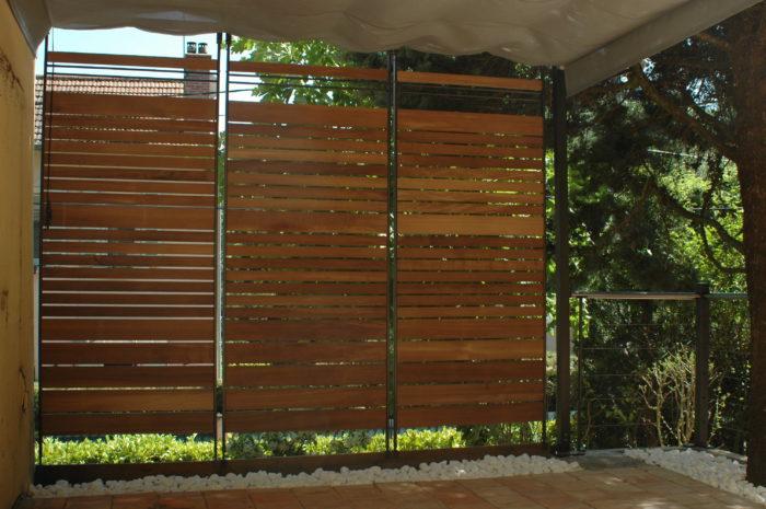 Exonido. Brise-vue en bois coupant d'un vis à vis plongeant sur la terrasse.