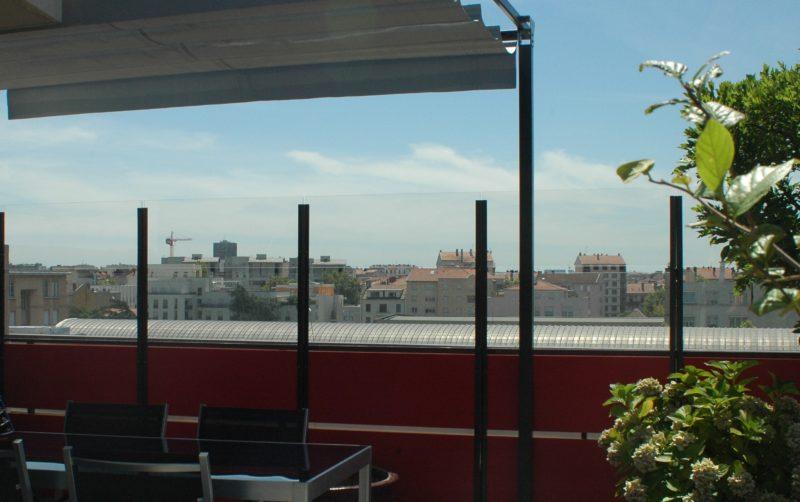 Panneau coupe vent transparent pour abriter une terrasse d'iammeuble plein sud