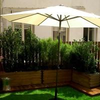 Cloisonnement aéré constitué d'étroites lames de pin fixées verticalement (hauteur 1,80m), habillé de végétaux persistants et faciles à vivre. Le parquet en pin bruni rehausse les jardinières en mélèze.