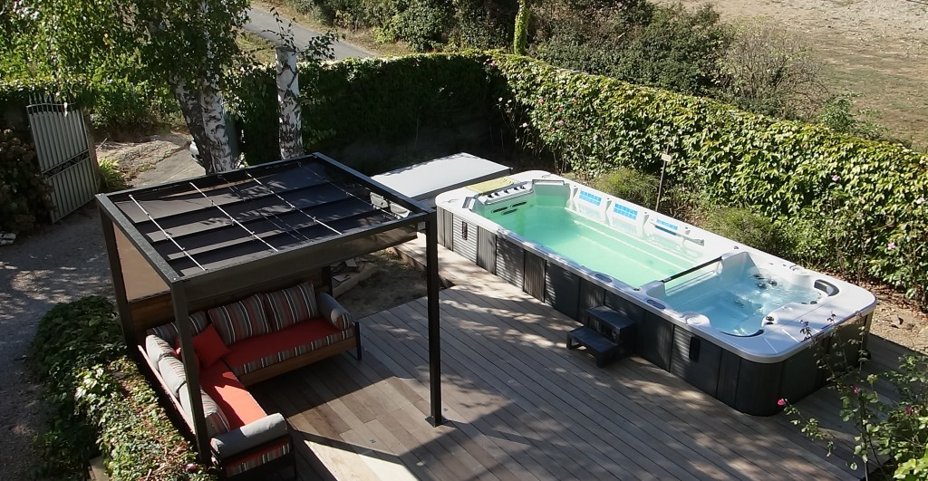 Aménagement de terrasse avec pergola, canapé, sol ipé et spa : un espace de détente aussi convivial que confortable